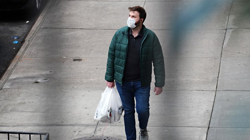 A man wears a protective mask while carrying a shopping bag during the coronavirus pandemic on April 18, 2020 in New York City.