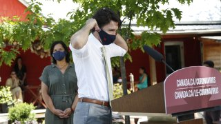 Justin Trudeau, Canada's prime minister, puts on a protective mask following a news conference in Chelsea, Quebec, Canada, on Friday, June 19, 2020. The federal government said earlier this month landlords had applied for only C$90 million ($66 million) from a rent assistance fund on behalf of about 26,000 tenants. That's less than 5% of its estimate of C$2 billion when the program was introduced in April.