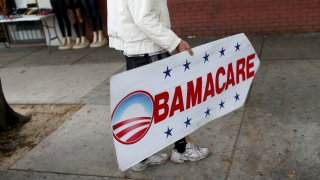 Pedro Rojas holds a sign directing people to an insurance company where they can sign up for the Affordable Care Act, also known as Obamacare, on Feb. 5, 2015, in Miami, Florida.