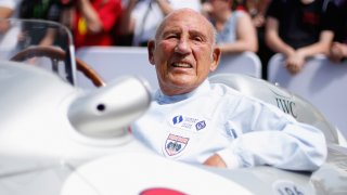Sir Stirling Moss sits in his Mercedes