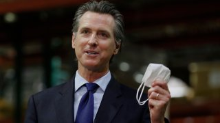 Gov. Gavin Newsom displays a face mask as he urges people to wear them to fight the spread of the coronavirus during a news conference in Rancho Cordova, Calif., Friday, June 26, 2020. Newsom said he wants Imperial County in Southern California to reimpose a stay-at-home order amid a surge in positive coronavirus tests.