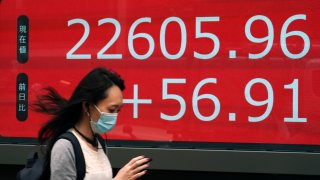 In this June 24, 2020, file photo, a woman walks past an electronic stock board showing Japan's Nikkei 225 index at a securities firm in Tokyo.
