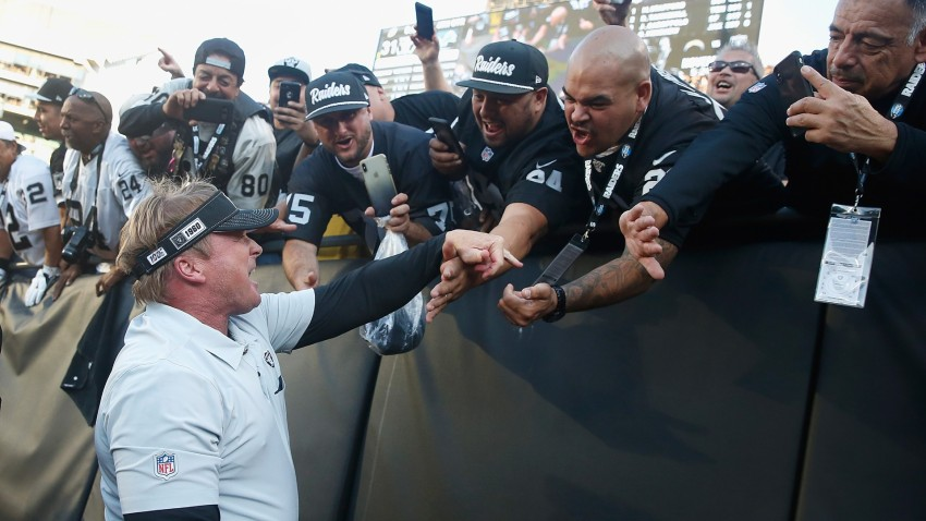 Jon Gruden of the Oakland Raiders celebrates with fans.