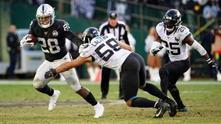 Josh Jacobs of the Oakland Raiders is tackled on a run.