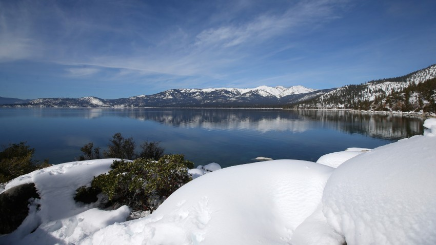 Snow covers the Sierra Nevada mountains and the shoreline of Lake Tahoe