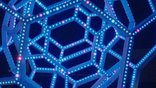 Blue LED sculpture made of concentric geodesic domes, seen at night