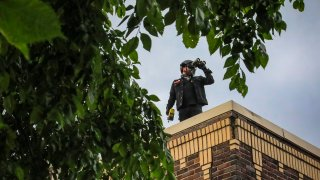 Obediah, a member of a neighborhood watch that started after the death of George Floyd in police custody sparked unrest, looks out from the roof of his home with binoculars, Tuesday June 2, 2020, in Minneapolis, Minn. A week of civil unrest has led some Minneapolis residents near the epicenter of the violence to take steps to protect their homes and neighborhoods.