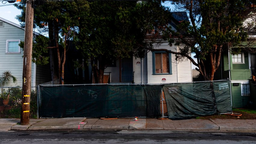 A newly-erected fence blocks the front of a vacant home that Moms 4 Housing activists occupied.