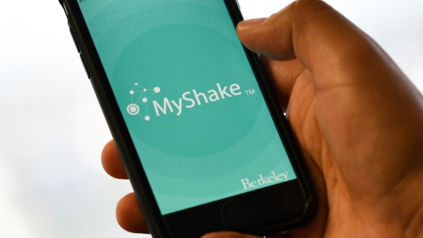 "A person checks the ""MyShake"" app on their smartphone."
