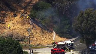Firefighters battle a brush fire in San Francisco's Potrero Hill neighborhood.
