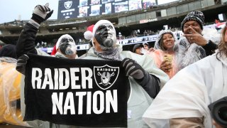 Oakland Raiders fans cheer in the Black Hole.