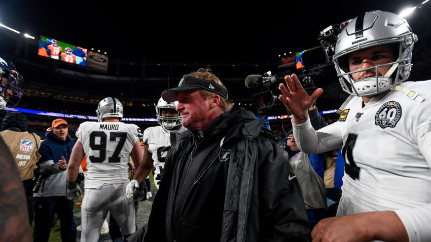 Head coach Jon Gruden of the Oakland Raiders walks onto the field with Derek Carr