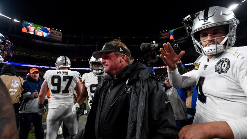 Head coach Jon Gruden of the Oakland Raiders walks onto the field with Derek Carr