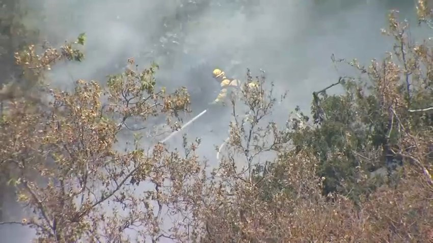 Firefighters battle a brush fire in unincorporated San Jose.