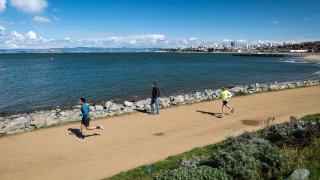 Joggers run past a pedestrian on a trail at Crissy Field in San Francisco.