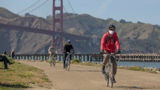In this April 27, 2020, file photo, people ride bicycles near the Golden Gate Bridge amid the coronavirus outbreak in San Francisco, California.
