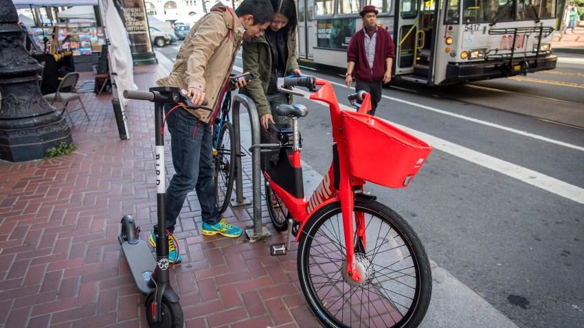 People unlock a bike in San Francisco.