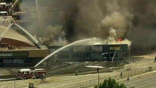 Firefighters battle a blaze at a strip mall in San Jose.