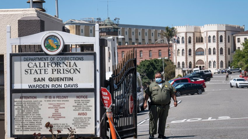 A California Department of Corrections and Rehabilitation (CDCR) officer wearing a protective mask stands at the front gate of San Quentin State Prison.