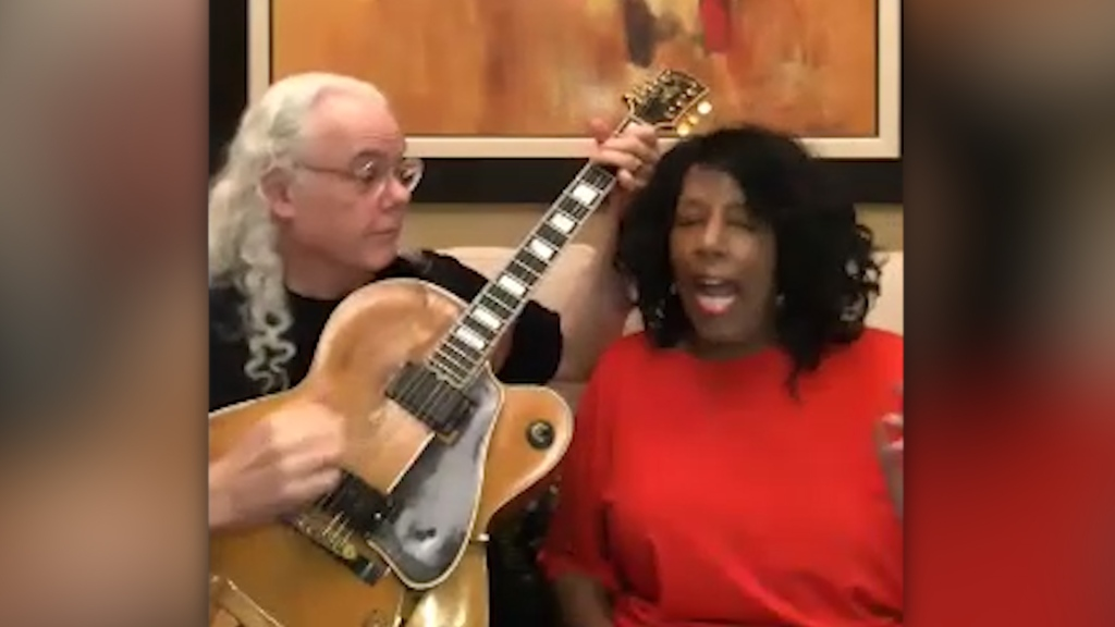a man with a guitar sits next to a woman singing in a red sweater.