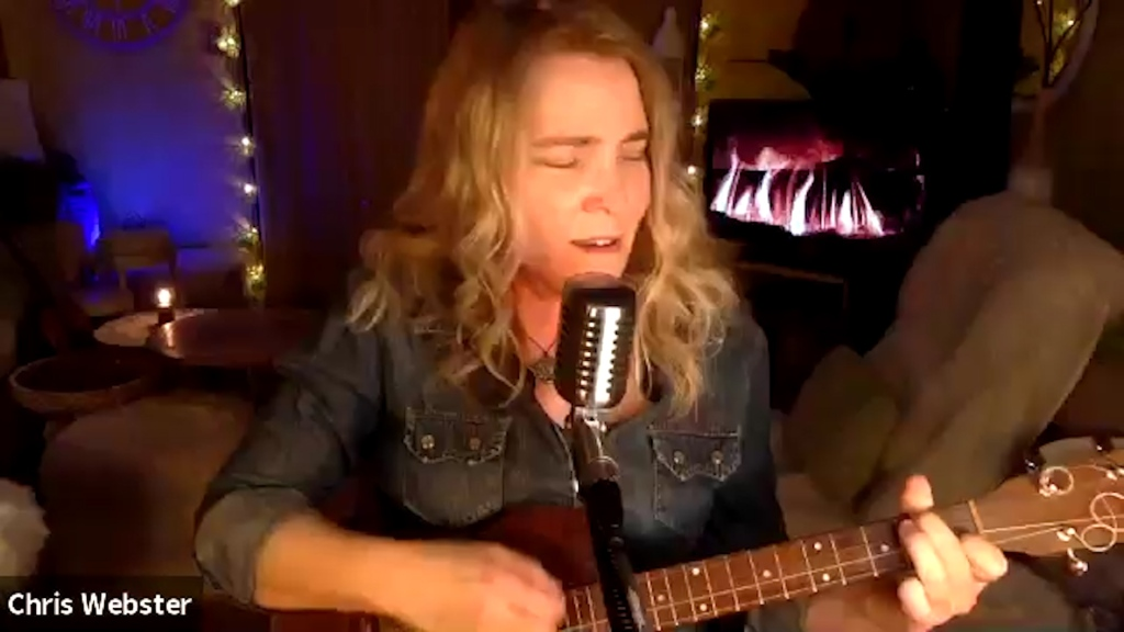 A woman plays a ukulele in front of a digital fireplace with christmas lights in the background