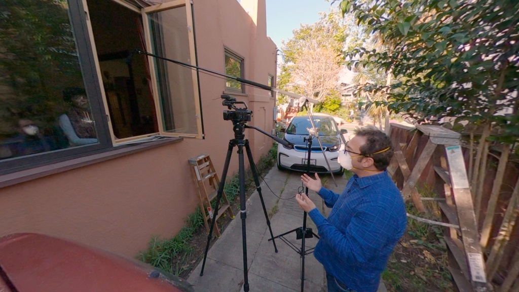 Reporter wearing a facemask stands outside a window with a tripod and microphone stand, interviewing a woman sitting in her home.