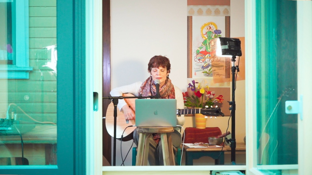 A woman sits at a laptop with her guitar. The camera is looking into her home from outside a window.