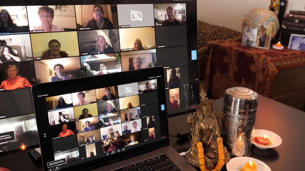 computer sits amid candles and meditation beads with a zoom video conference on the screen