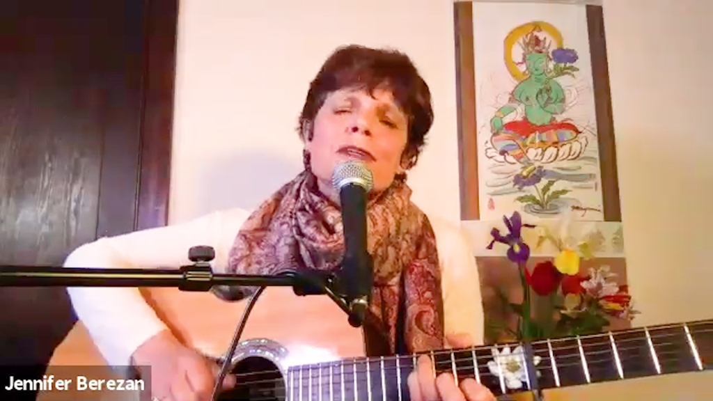 A woman with a guitar sings in front of a microphone while sitting at home.