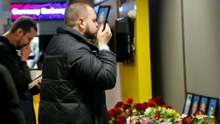 In this Jan. 8, 2020, file photo, the partner of Julia Sologub, a member of the flight crew of the Ukrainian 737-800 plane that crashed on the outskirts of Tehran, kisses a portrait of her at a memorial inside Borispil international airport outside Kyiv, Ukraine.