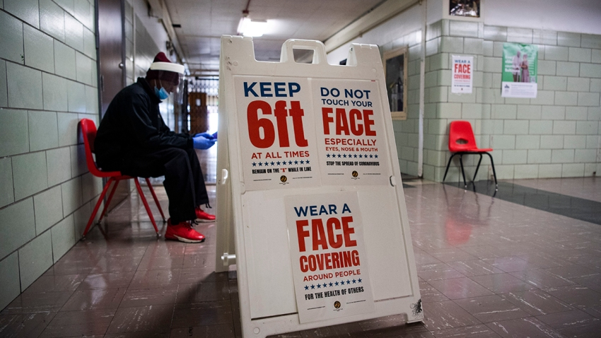 A sign reminds voters to practice social distancing during the election to fill the remainder of the late Rep. Elijah Cummings' term, April 28, 2020, at Edmondson High School in Baltimore, Md.
