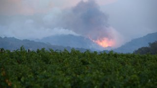 Hills above vineyard ignite