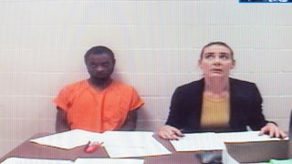 In this Sept. 13, 2019, file photo, Tevin Biles-Thomas, left, shown on a video monitor, listens to his arraignment with public defender Alonda Bush from the Cuyahoga County jail as the hearing is held in Common Pleas Court in Cleveland. Biles-Thomas is accused of killing three people at a New Year's Eve party in 2018 and is the older brother of U.S. Olympic gymnast Simone Biles.