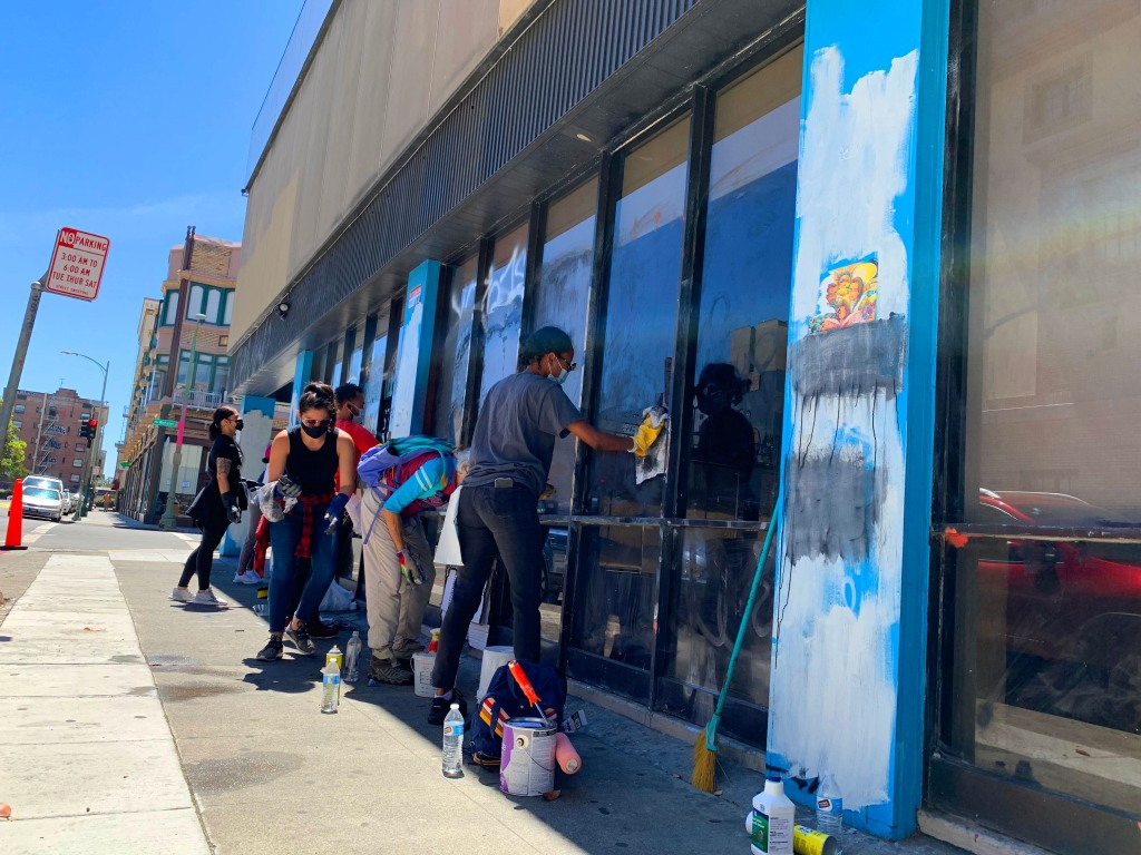 A group of volunteers remove graffiti from a building in Oakland's downtown.