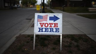 """In this Aug. 14, 2018, file photo, a sign reading """"Vote Here"""" points toward a polling place for the 2018 Minnesota primary election at Holy Trinity Lutheran Church in Minneapolis, Minnesota."""