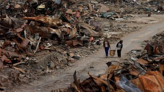 In this Thursday, April 7, 2011, file photo, two women walk past debris in an area devastated by the March 11 earthquake and tsunami in Ishinomaki, Miyagi Prefecture, northern Japan.