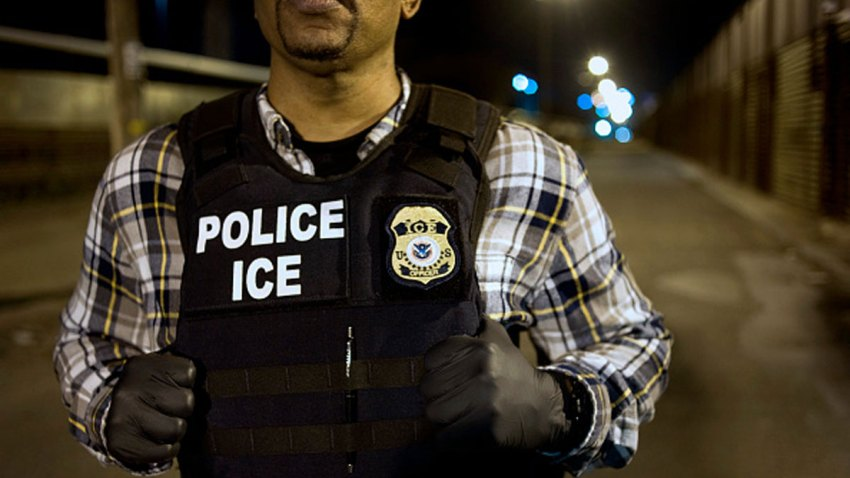 A U.S. Immigration and Customs Enforcement (ICE) agent waits as a group of undocumented men, not pictured, are deported to Mexico at the U.S.-Mexico border in San Diego, California, U.S., on Thursday, Feb. 26, 2015.