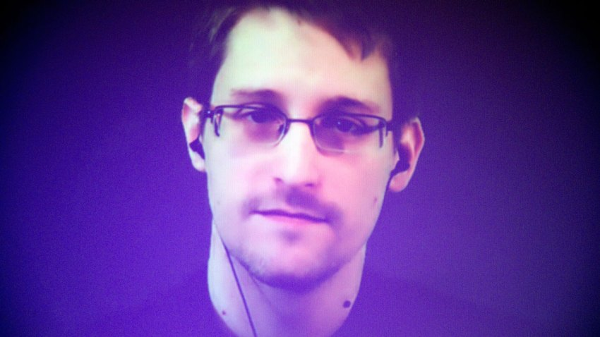 In this Dec. 10, 2014, file photo, former U.S. National Security Agency contractor Edward Snowden, who is in Moscow, is seen on a giant screen during a live video conference for an interview as part of Amnesty International's annual Write for Rights campaign at the Gaite Lyrique in Paris, France.