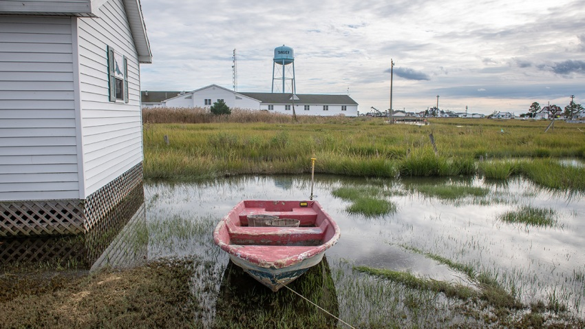 An empty rowboat sits atop the water-soaked ground alongside a house and a water tower stands in the distance in this undated photo from tiny Tangier Island, Virginia.