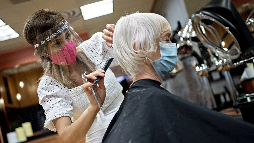 A stylist wearing a protective face shield and mask cuts a customers hair at a salon in Arlington, Virginia, U.S., on Friday, May 29, 2020.