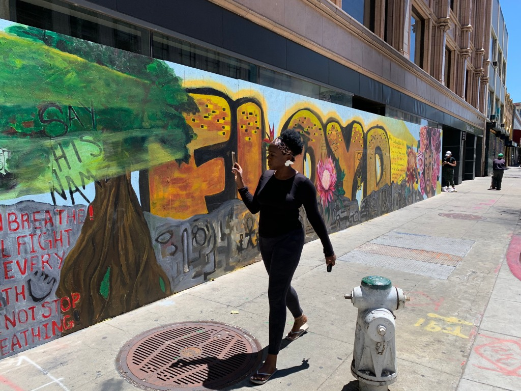 A woman takes a picture of a mural honoring George Floyd in downtown Oakland.