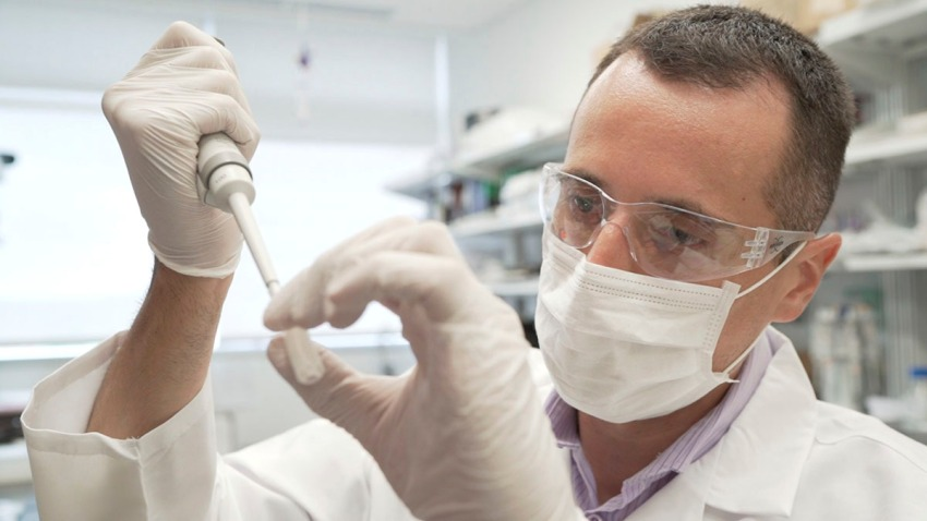 In this image from video provided by Washington University, researcher Nicolas Barthelemy works on a p-tau217 test for Alzheimer's disease at a laboratory in St. Louis, Mo., July 27, 2020.