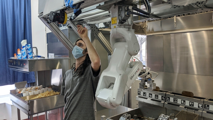 A technician makes an adjustment to a robot at Miso Robotics' White Castle test kitchen in Pasadena, California, July 9, 2020. Robots that can flip burgers, make salads and even bake bread are in growing demand as virus-wary kitchens try to put some distance between workers and customers.