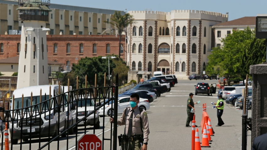 a correctional officer closes the main gate at San Quentin State Prison in San Quentin, Calif.