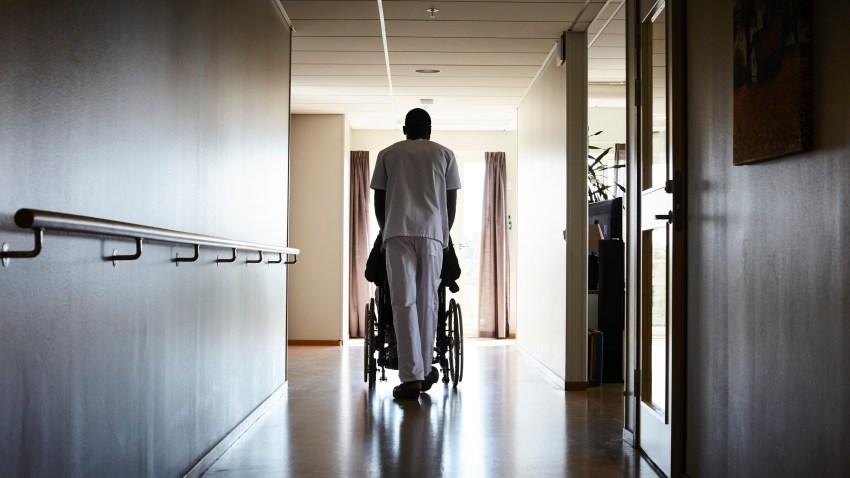 Full length rear view of male nurse pushing senior man on wheelchair at hospital corridor