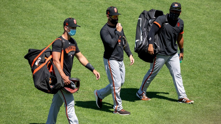 San Francisco Giants catcher Buster Posey walks with manager Gabe Kapler and another player.