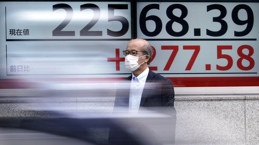 In this July 13, 2020, file photo, a man wearing a face mask to help curb the spread of the coronavirus stands near an electronic stock board showing Japan's Nikkei 225 index at a securities firm in Tokyo.