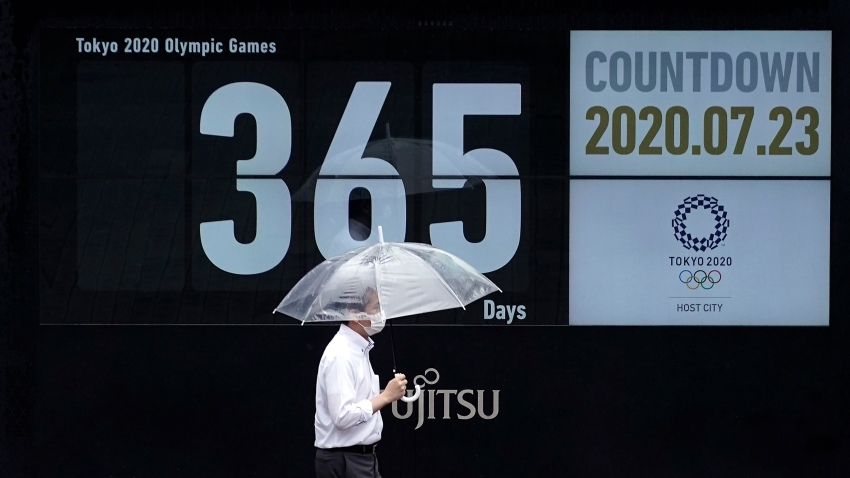 A man wearing a mask against the spread of the new coronavirus walks in front of a countdown calendar showing 356 day to start Tokyo 2020 Olympics Thursday, July 23, 2020, in Tokyo. The postponed Tokyo Olympics have again reached the one-year-to-go mark.
