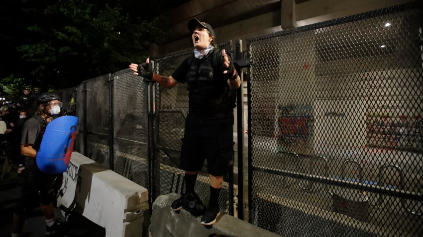 A demonstrator rallies a crowd in front of a steel fence during a Black Lives Matter protest at the Mark O. Hatfield United States Courthouse Tuesday, July 28, 2020, in Portland, Oregon.