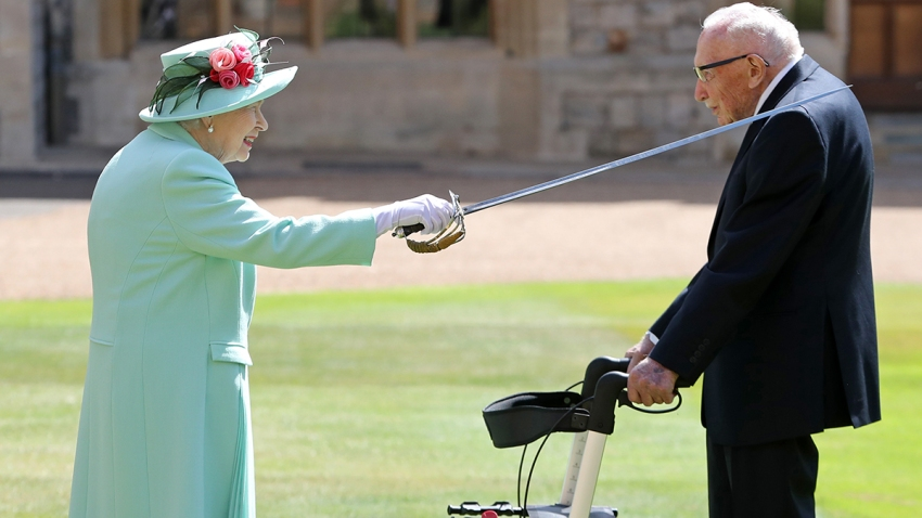 Britain's Queen Elizabeth II uses the sword that belonged to her father, George VI, as she confers the Honour of Knighthood on 100-year-old WWII veteran Captain Tom Moore at Windsor Castle in Windsor, west of London, on July 17, 2020.
